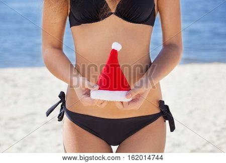 Young, attractive, slender girl in a black bathing suit holding small hat Santa Claus. New Year holidays and tourism.