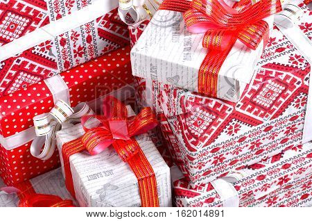 New Year gifts. A lot of red boxes with gifts for the new year. The traditional preparation of gifts under the Christmas tree in New Year's Eve