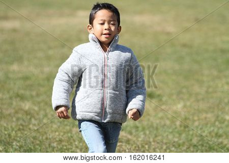 Japanese boy running on the grass (first grade at elementary school)