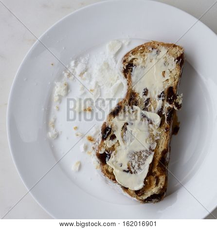 Some buttered stolen on a white plate.