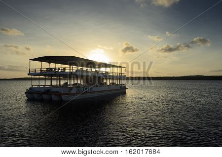 Joao Pessoa PB Brazil - December 8 2016: Tour boat that transports people on sailing tours in the waters of Praia do Jacare Beach. Photograph of boat on sunset on a beautiful day.