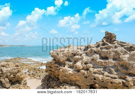 Rocks pierced by the waves of the sea. Holes in the rocks caused by the impact with waves of the sea. Beach of Joao Pessoa PB Brazil.