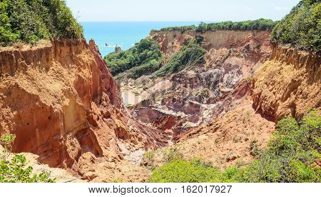 Canyon Of Cliffs With Many Stones Sedimented By Time, Rocks With Red And Yellow Colors And The Sea I