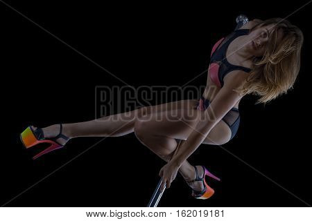 Professional pole dancer dancing isolated on black background
