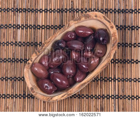 Jumbo pitted kalamata olives in olive wood bowl on bamboo placemat