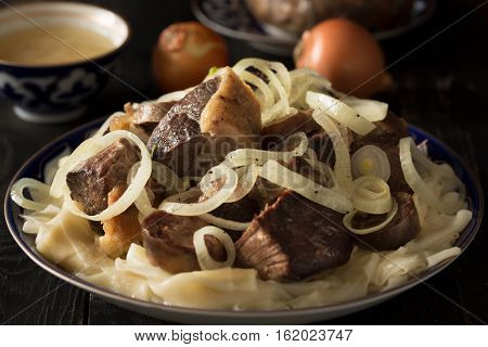 National Kazakh dish - Beshparmak prepared with boiled meat, pasta and onuin