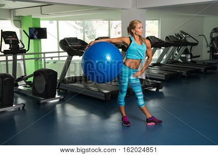 Woman Doing Heavy Weight Exercise On Ball