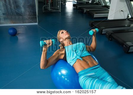 Mature Woman Doing Exercise On Ball In Gym