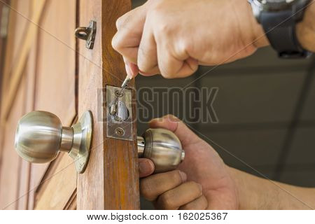 close-up locksmith repair silver lock on wood door - can use to display or montage on product