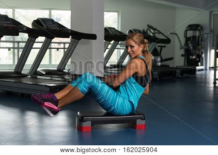 Female Doing Abdominal Exercise With Ball On Stepper