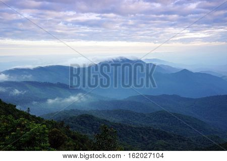 Mountain landscape with wave of fog and dark cloudy sky on the top of mountain with the view into misty valley. Doi Inthanon National Park Chiang Mai Thailand