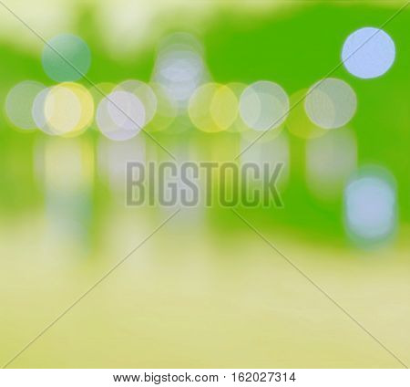 Abstract multicolor blurred bokeh light with water reflection green yellow background