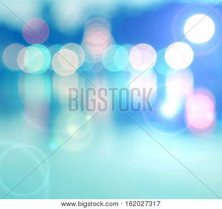 Abstract multicolor blurred bokeh light with water reflection and lens flare effect on blue background