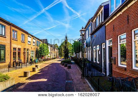 Quiet street in the historic Dutch Fishing Village of Bunschoten-Spakenburg with Renovated Row Houses on a Sunny Summer day