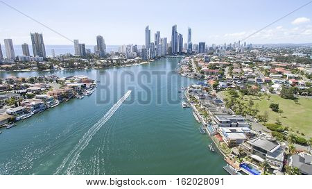 Aerial view of Gold Coast waterways between Macintosh and Cronin Islands with a speed boat heading towards Surfers Paradise