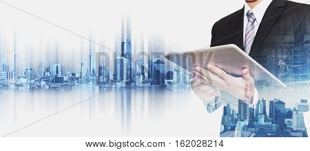 Businessman working on digital tablet with double exposure Bangkok city, concepts of real estate business development