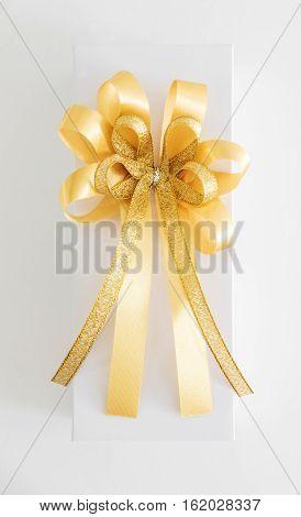 White gift box with golden ribbon bow, on whitebackground
