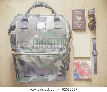Bagpack with passport notebook watch sunglasses and handkerchief on wooden table.