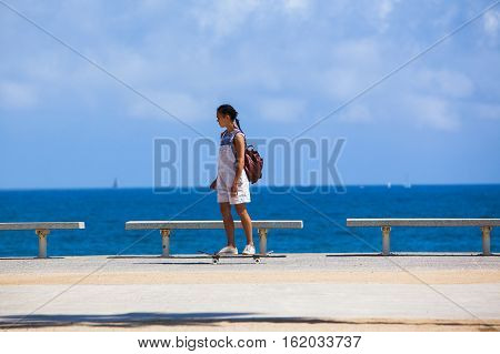 BARCELONA SPAIN - MAY 30 2016: YOUNG GIRL RIDE SKATEBOARD ON THE SIDEWALK AT LA BARCELONETA MAY 30 2016 IN BARCELONA SPAIN