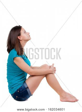 sad brunette woman in shorts sitting on floor and looking up. Isolated over white background