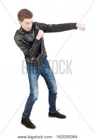 skinny guy funny fights waving his arms and legs. Isolated over white background. Man shoots with his right hand.