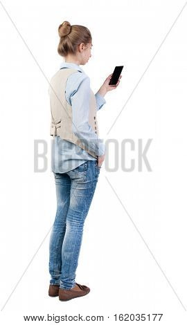 back view of standing young beautiful  woman  in vest and using a mobile phone. girl  watching. Rear view people collection.  backside view of person.  Isolated over white background. Bored girl