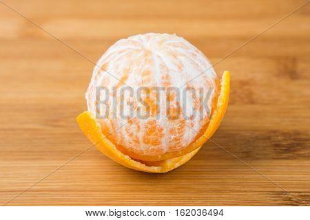 One Navel Orange Peeled Isolated On Wood Background