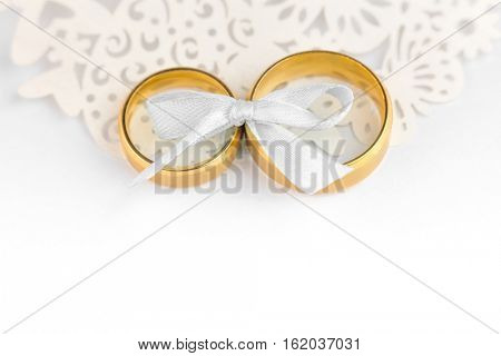 Gentle Wedding Celebration background - pair of wedding rings with bow and copy space for text