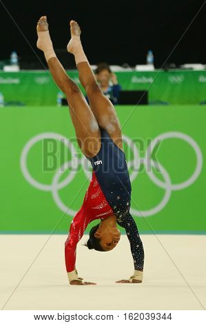 RIO DE JANEIRO, BRAZIL - AUGUST 7, 2016: Olympic champion Gabby Douglas of United States competes on the floor exercise during women's all-around gymnastics qualification at Rio 2016 Olympic Games