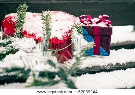 A gift box with red heart shaped tin box and a fragment of a pine-tree branch on a bench covered with snow