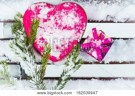Pink heart shaped tin box with a gift box and a fragment of a pine-tree branch on a bench covered with snow