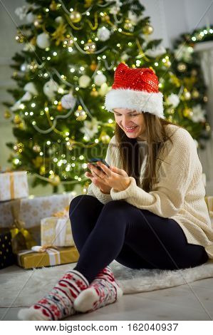 Christmas Eve. Nice girl in Santa's cap sits near Christmas tree with the mobile phone in hands. House is decorated by holiday. Under Christmas tree there are a lot of gifts. Girl joyfully smiles.
