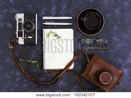 Flat lay top view office table desk. Desk workspace with retro camera diary pen glasses case cup of coffee rosemary on dark background.
