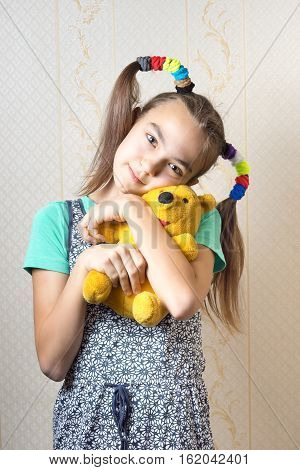 happy 11 year old girl hugging a yellow teddy bear toy