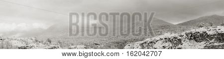 black and white panoramic photo landscape of wooded hills in the snow and the clouds and the mountain village in the Caucasus