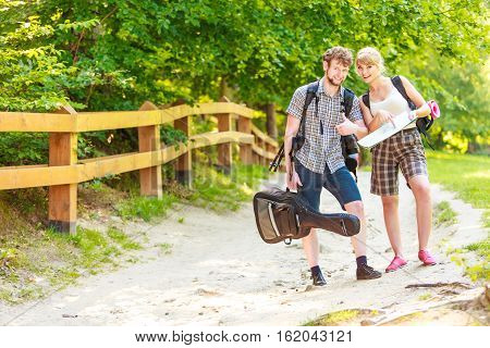 Man and woman tourists backpackers reading map on trip. Young couple hikers searching looking for direction guide. Backpacking summer vacation travel.
