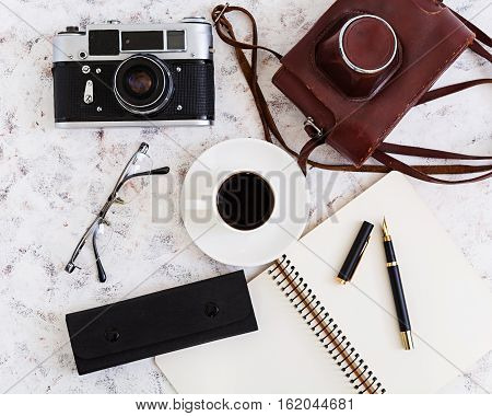 Flat lay top view office table desk. Desk workspace with retro camera diary pen glasses case cup of coffee on white background.