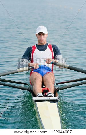 Single scull rowing competitor in action, toned image, vertical