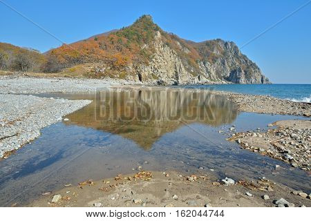The landscape on sea: beach with stones rocky cape seawater.