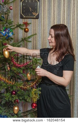 Woman decorates a Christmas tree Christmas decorations