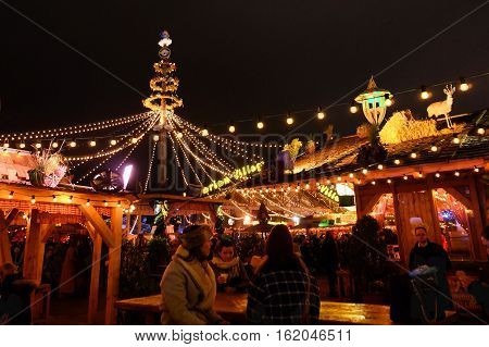 LONDON UK - DECEMBER 14 2016: People at Winter Wonderland in Hyde park enjoy food and drink at night during Christmas and New years celebrations in London United Kingdom.