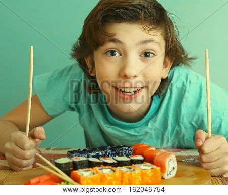 preteen handsome boy with sushi roll set and stick hungry