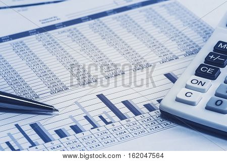 Accounting financial banking banker bank stock spreadsheet data with pen and calculator in blue analysis analyzer calculations