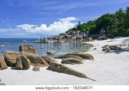 beautiful rocky beach with palm trees behind on ko samui island in the gulf of thailand