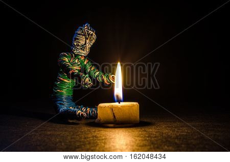 a little puppet man getting warm by candle fire
