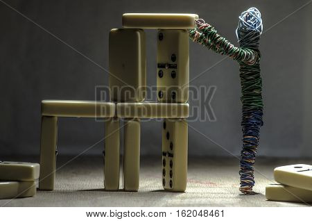 little puppet man building with domino parts