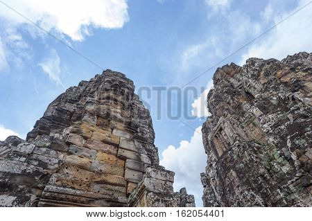 A horizontal photographic image of 2 large sculpted stone towers at Bayon Temple in Angkor Thom which is close to Angkor Wat near Siem Reap in Cambodia.