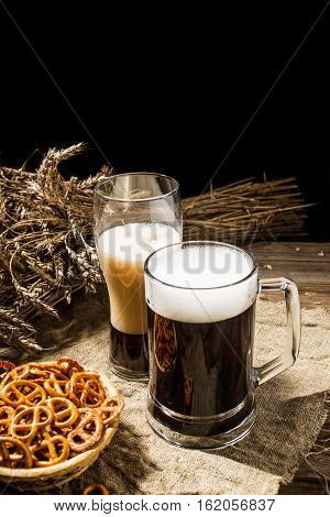 Mug and glasse beer with basket of pretzels and wheat on linen cloth on wooden background