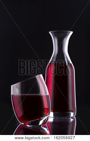 Decanter and glass with red drink on a black background