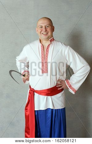 MOSCOW RUSSIA - MARCH 4,2013:farmer with a sickle in the Russian national costume